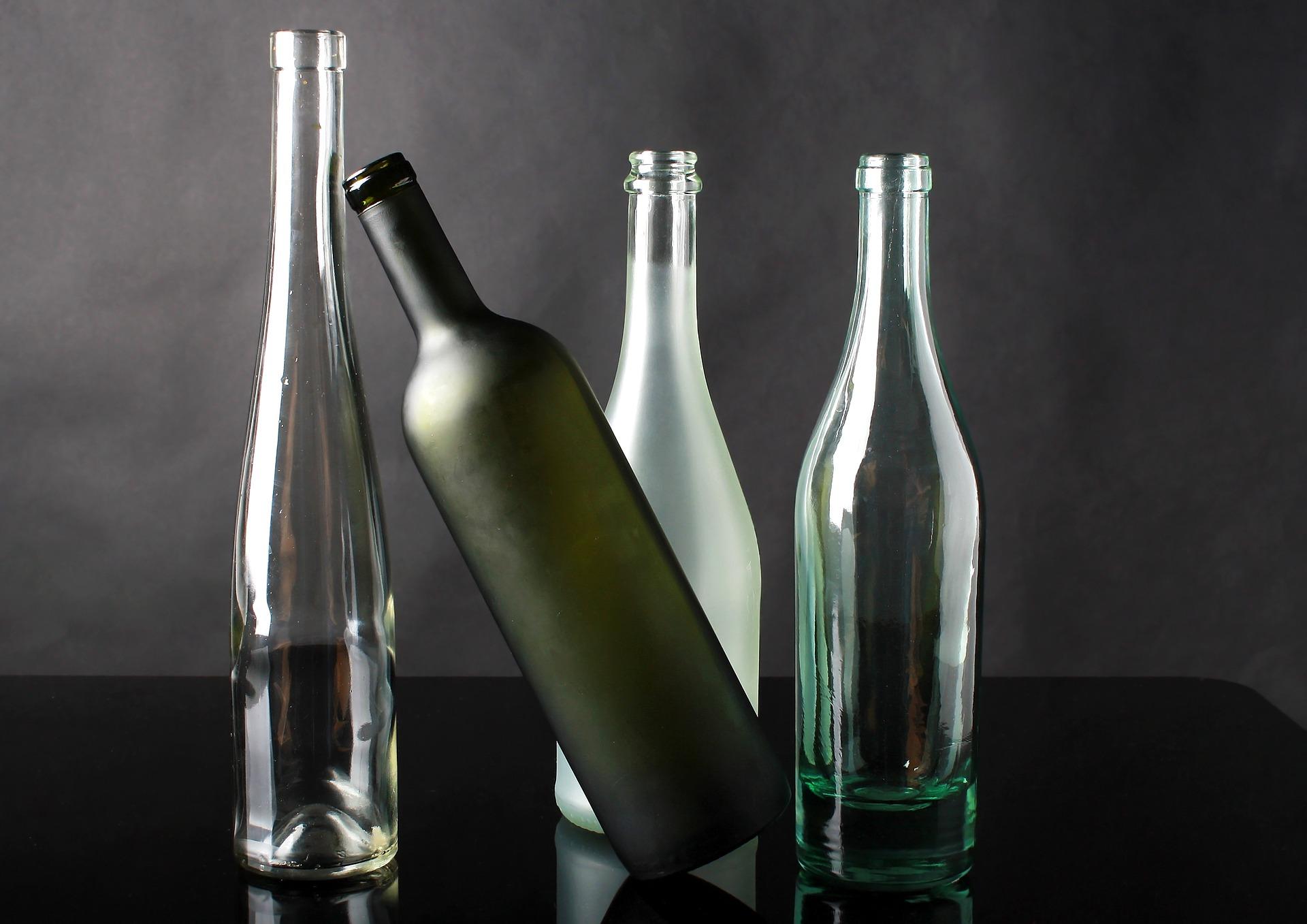 Kuvituskuva tyhjiä lasipulloja rivissä, yksi pullo on kaatumassa.
