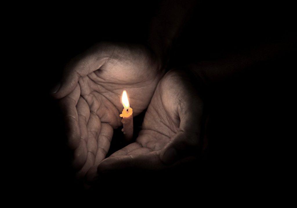 Kuvituskuva kynttilä kämmenellä
