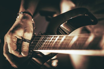 Kuvassa käsi soittaa kitaraa.