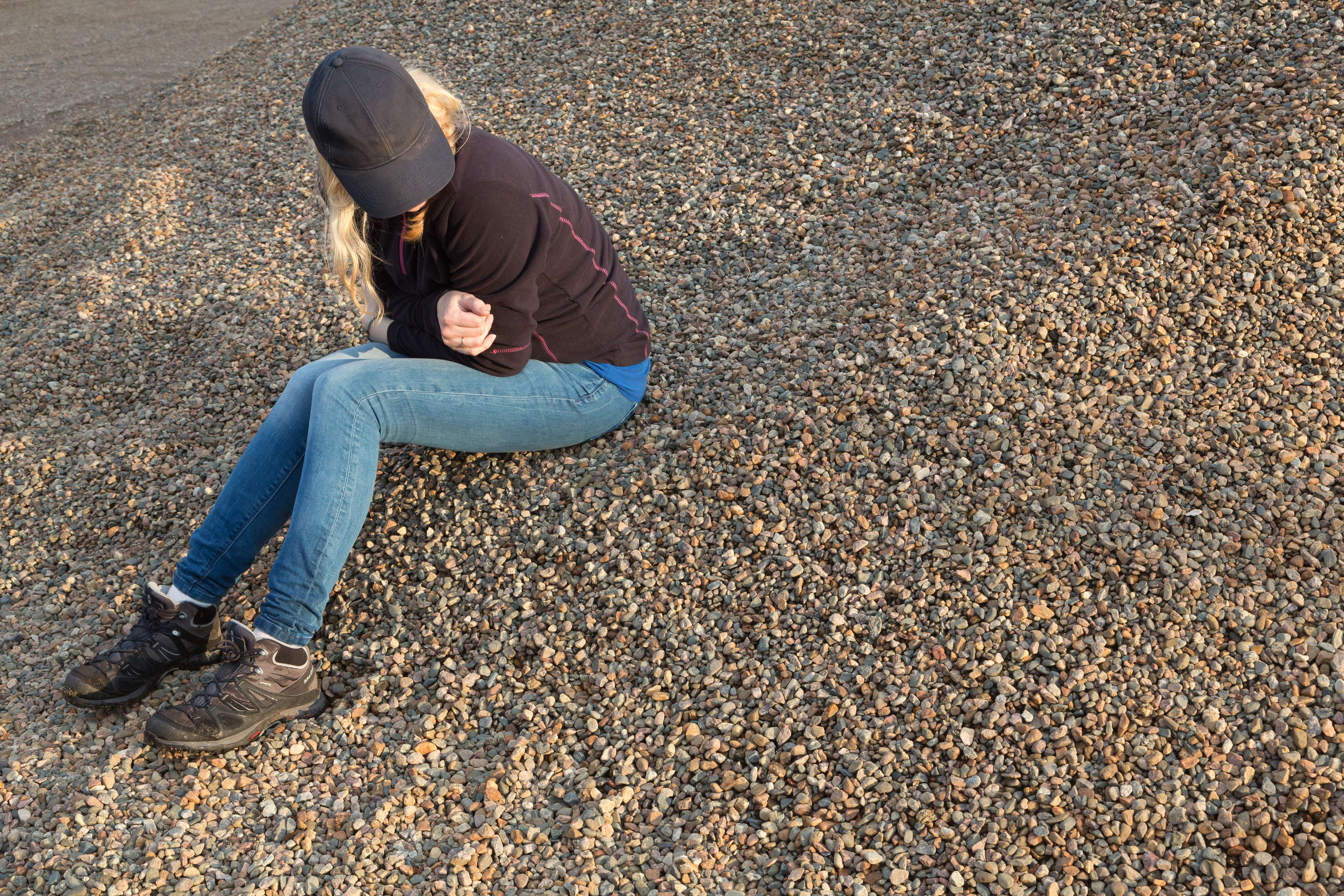 Nainen istuu rannalla ja katsoo vieressään olevaa hiekkaa.