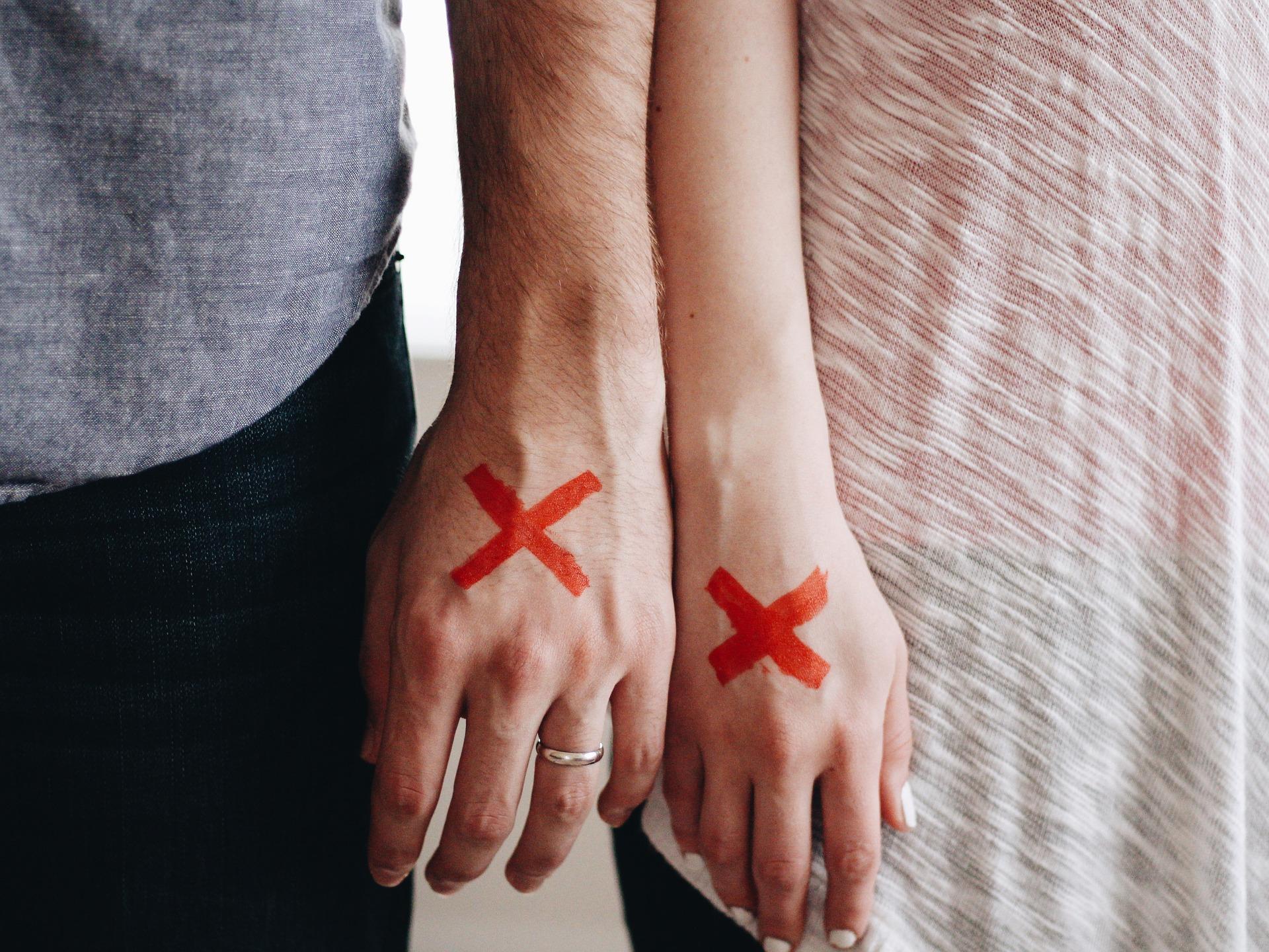 Kuvituskuva Kädet vierekkäin, kämmenselissä punainen rasti