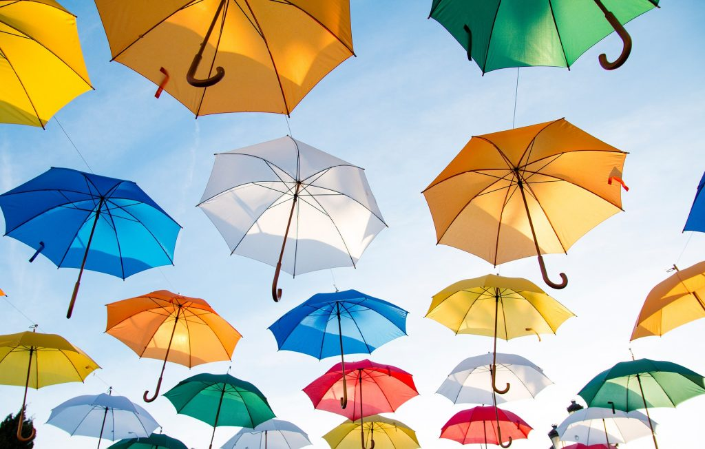 Kuvituskuva värikkäitä sateenvarjoja taivaalla