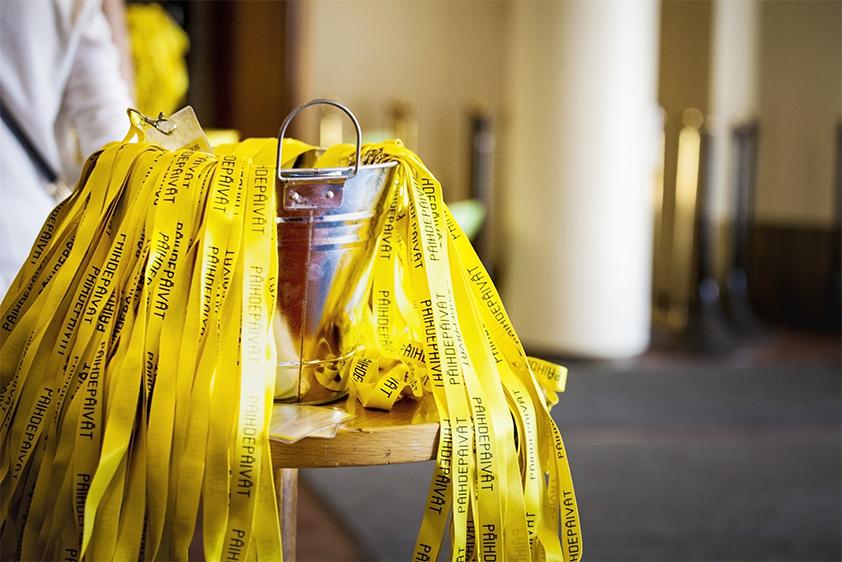 Kuvassa on metallisanko puupöydällä. Sangossa on Päihdepäivien keltaisia avainnauhoja.