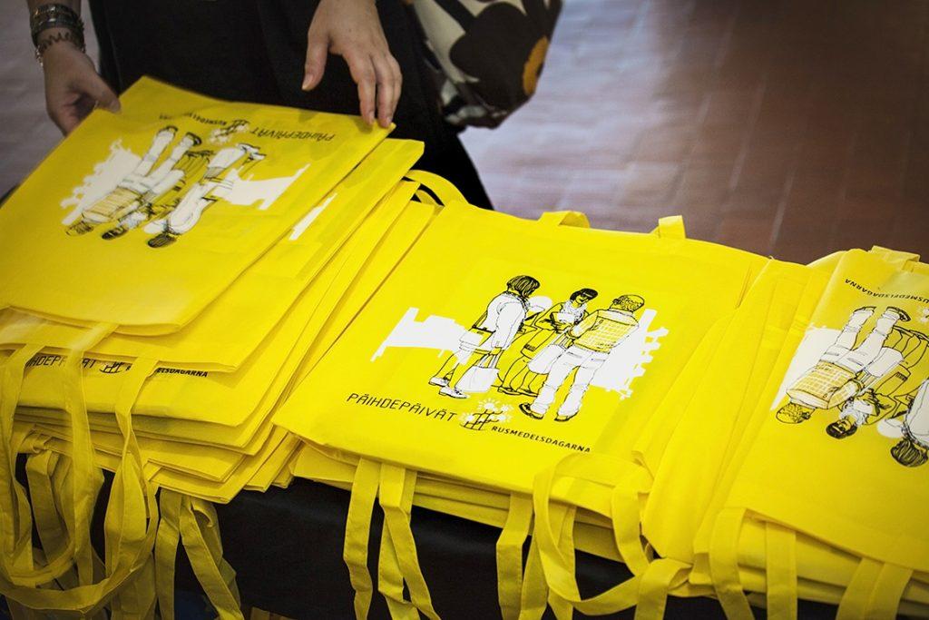 Kuvassa näkyy Päihdepäivien keltaisia kangaskasseja kolmessa pinossa