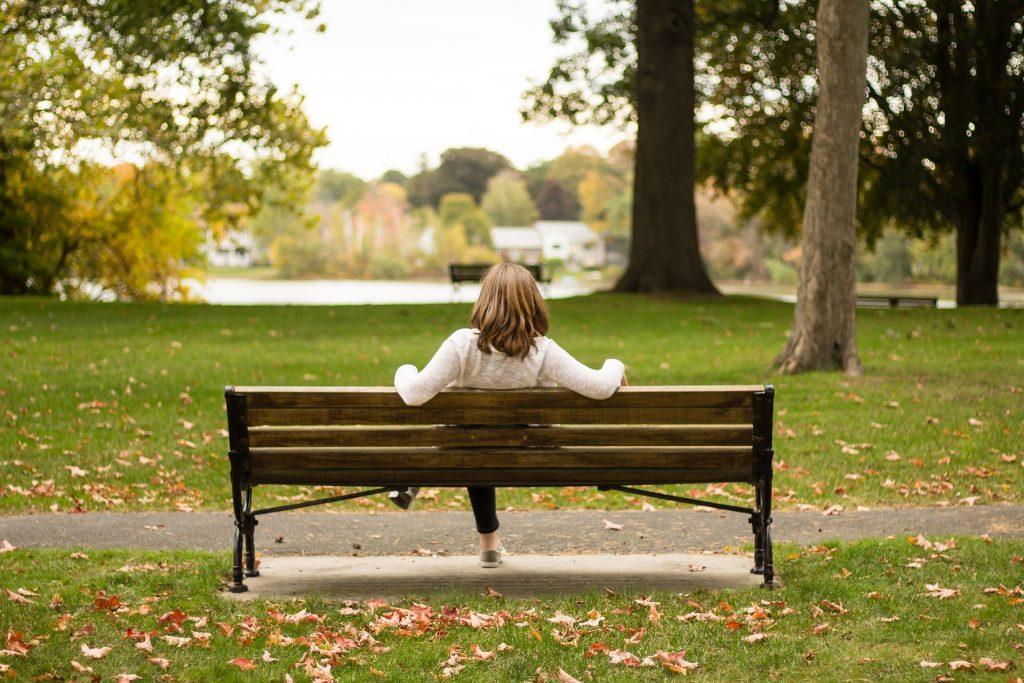 Nainen istuu puistossa yksin