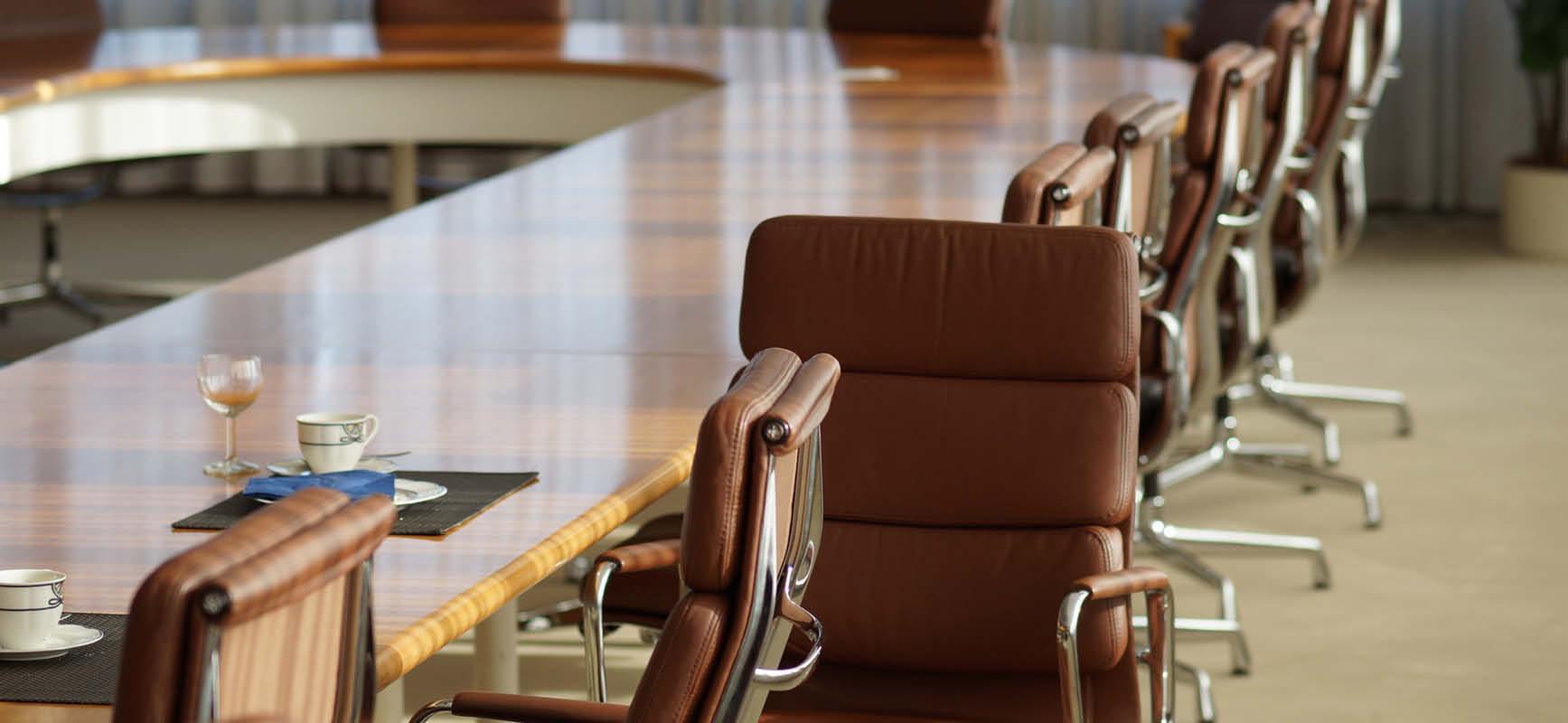 Kuvassa tyhjä kokouspöytä ja tuolit.