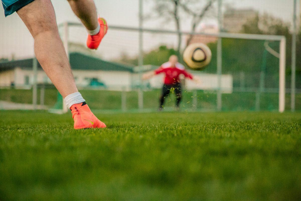 Kuvassa mies potkaisee pallon kohti maalia.