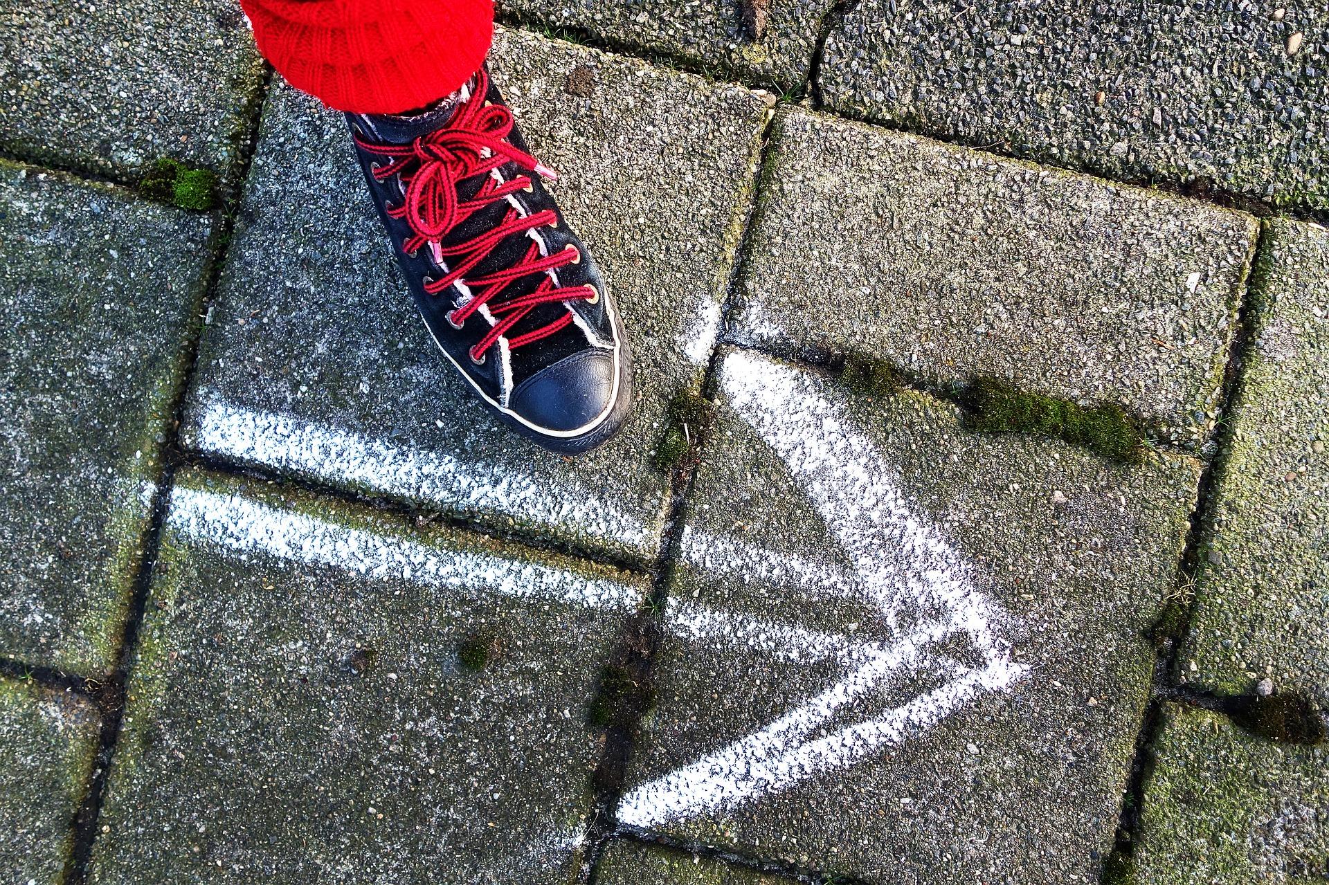 Kuvassa jalka ja katuun piirretty nuoli.