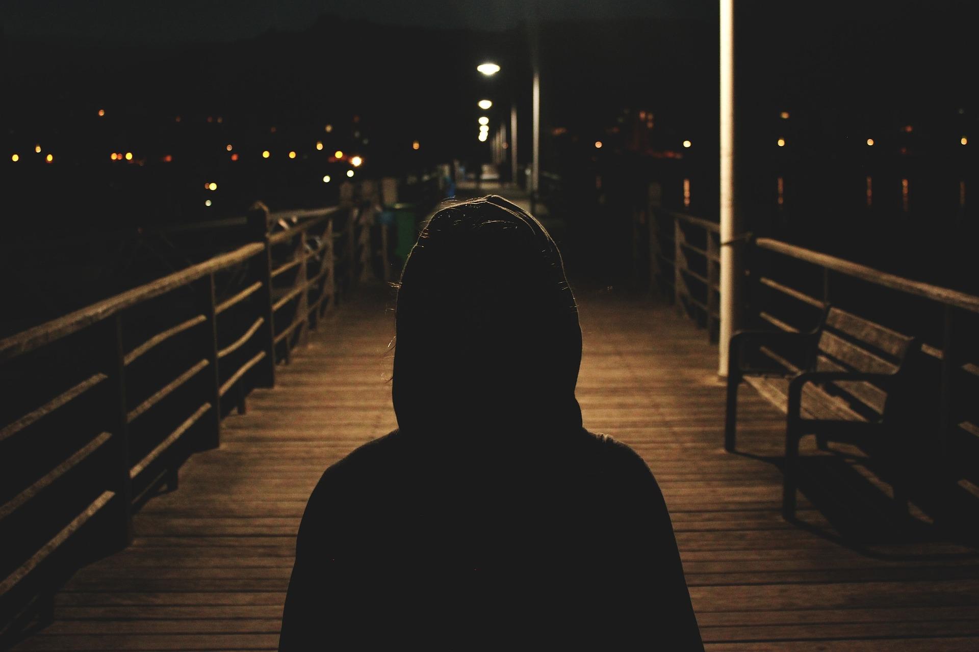 Tummaan huppariin pukeutunut ihminen katselee öistä kaupunkia.