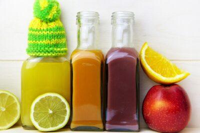 Eri värisiä hedelmämehuja lasipulloissa