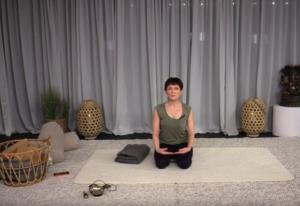 Yin Yoga -harjoitusvideo. Videon on tuottanut Yoga Nordic. Kuvassa ohjaaja istuu aloitusasennossa joogamatolla.