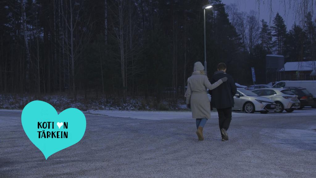 Kuvassa kaksi ihmistä kävelee vierekkäin kadulla sekä Koti on tärkein -kampanjan logo.