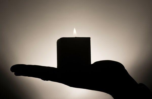 Käsi kannattelee kynttilää