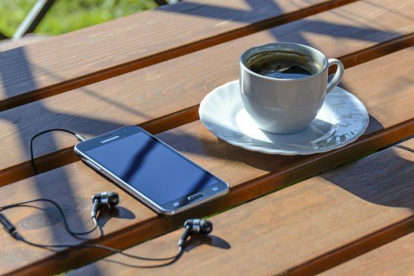 Kahvikuppi, kännykkä ja korvanappikuulokkeet.