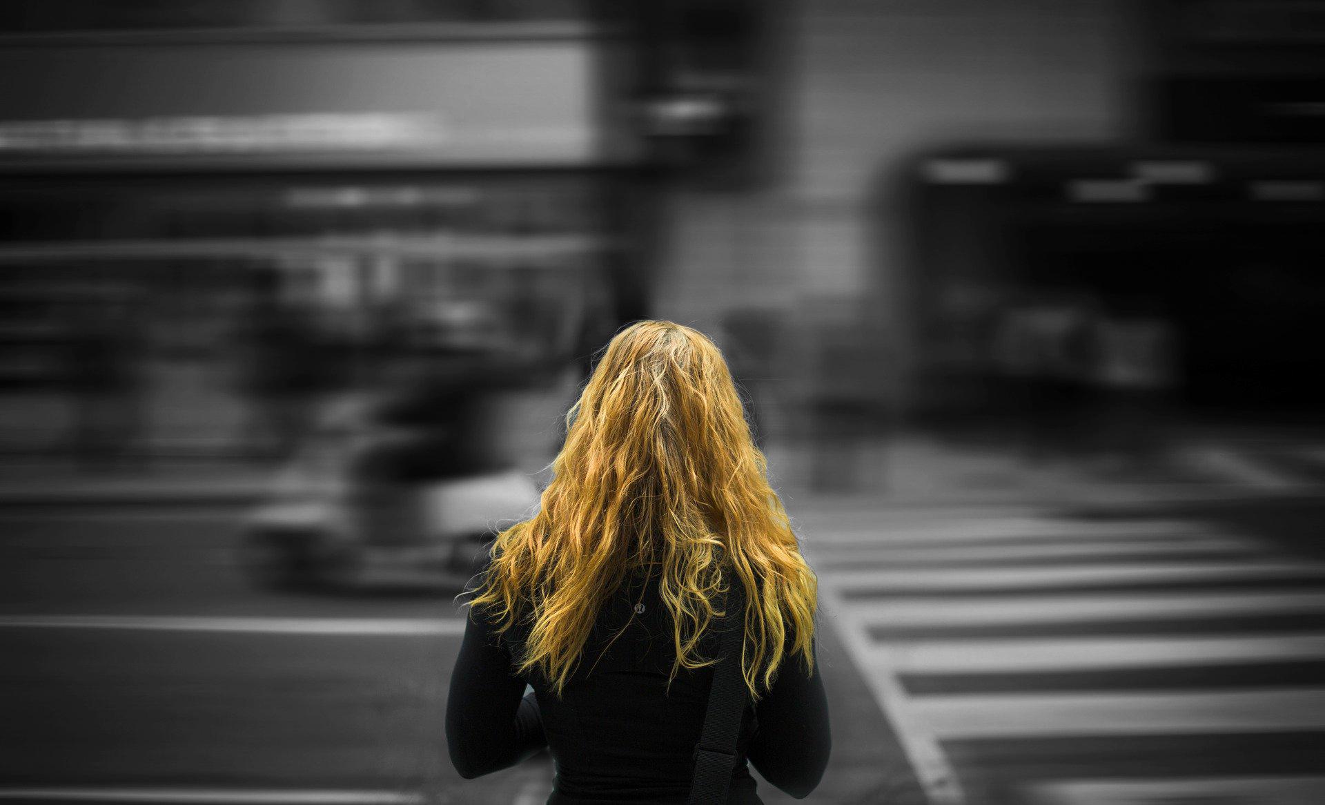 Kuvassa nuori nainen seisoo selin ja katsoo kohti suojatietä.