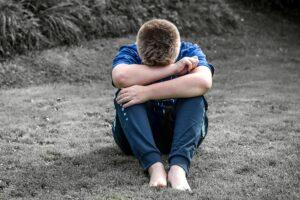 Nuori poika istuu maassa ja on painanut pään käsiinsä.