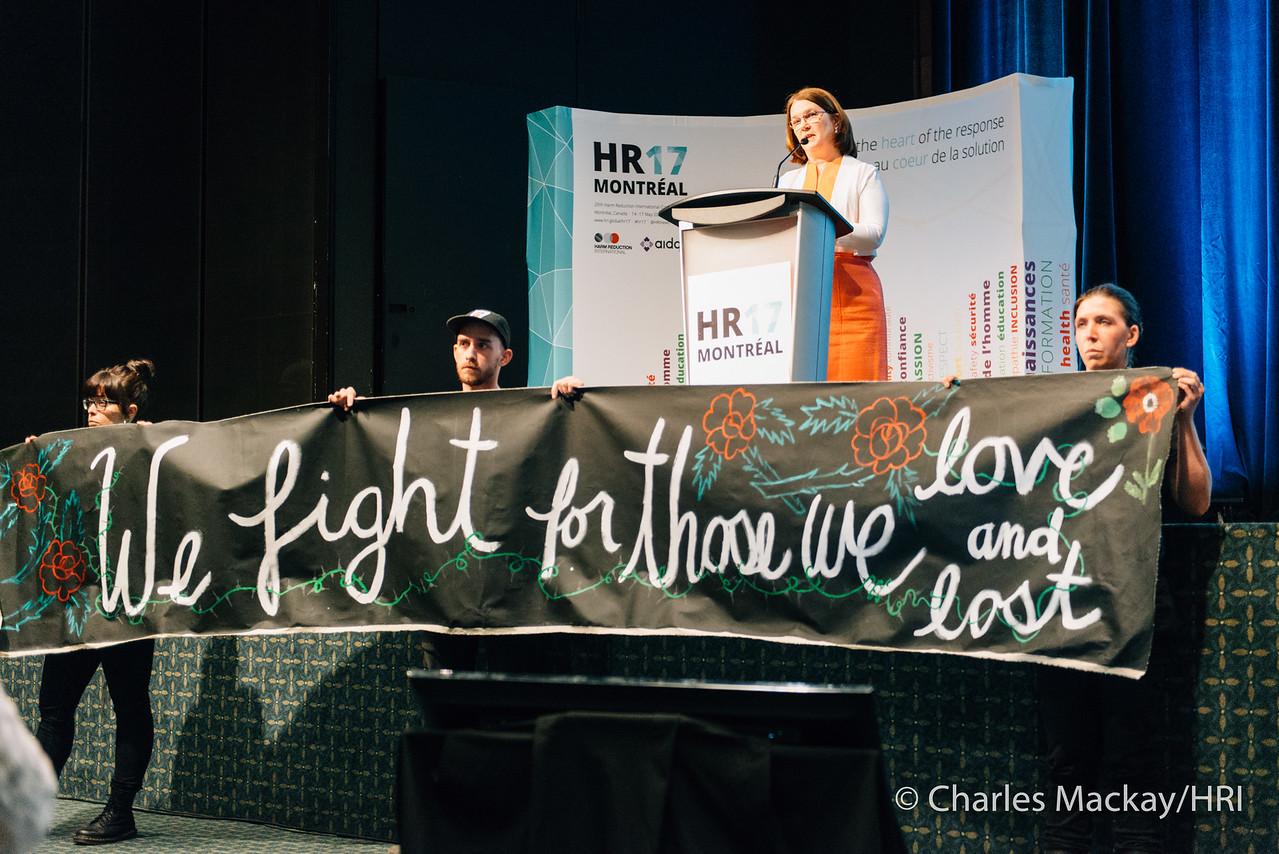 Kuvassa protestoijat pitävät käsissään banderollia, jossa lukee teksti We Fight for Those We Lost and Love. Kanadan terveysministeri pitää kuvassa puhetta.