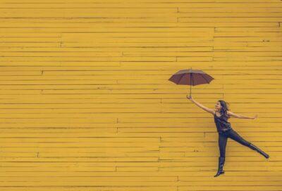 Kuvassa tyttö pitää sateenverjoa okran värisen seinän edessä.